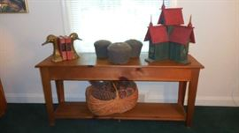 "Family Room: This long narrow pine table has an under-shelf and measures 60"" wide x 16"" deep x 27"" tall.  The heavy brass goose-head bookends, three spools of string, the red/green bird house, and the large basket of pine cones are also priced for sale."
