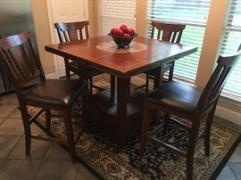 Nice Pub or bar style dining table & 4 chairs. In great condition! Table has marble lazy susan in the center and drawer at the base.