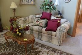 Sofa, pillows, coffee table, end table, table lamp, sofa table, floral arrangements
