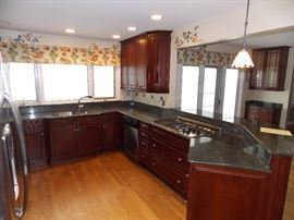Beautiful Cherry Kitchen Cabinets, Granite Counter Tops, Side by side Stainless Steel GE  refrigerator, KitchenAid double oven, Stainless Steel KitchenAid dishwasher and a Stainless Steel Thermodor cooktop.