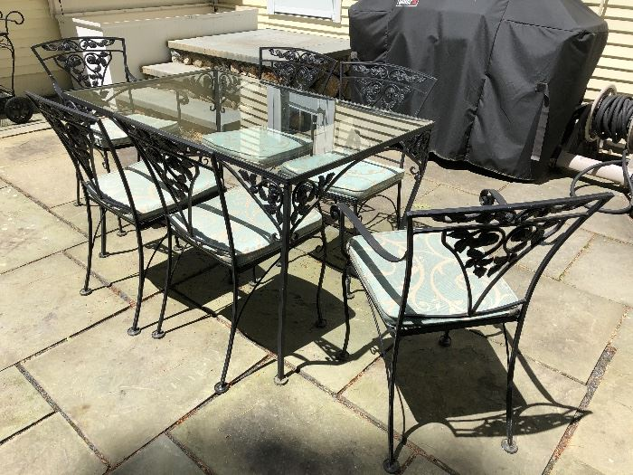 Vintage wrought iron, glass top table with matching chairs.