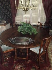 Exceptionally large round antique dining table; comfortable for 8 chairs (4 chairs showing)