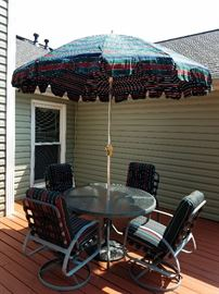 Glass top, round patio set with four chairs, umbrella, and cushions.
