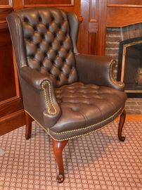 One of a pair of leather wing back chairs
