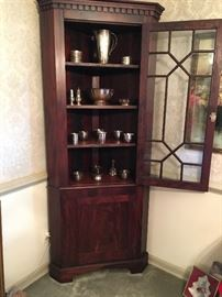 Antique corner cabinet with doors open. Dates to late 1800's. Excellent condition. Silverplate and sterling on shelves.