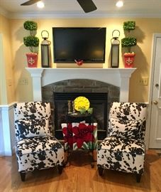 Custom upholstered cow-print armless chairs. Boutique topiary décor, hooked decorative pillows. The TV in this image is NFS but a different Sony flat screen is available!