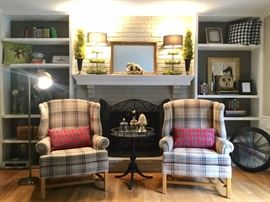 Custom upholstered wingbacks in a burberry-style pattern, throw pillows, painted pie table, topiaries.