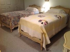 Drexel twin beds with quilts.