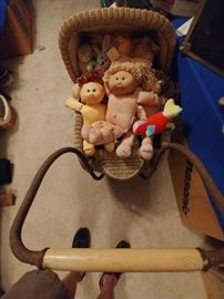 Cabbage patch kids in basket cradle.