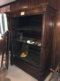 Antique armoire. Doors are leaning against it.