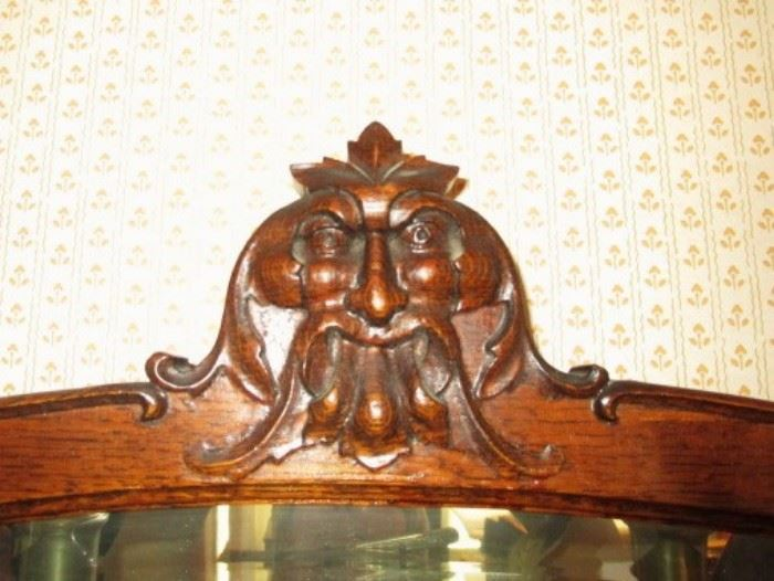 Carved Face on top of curved glass china cupboard
