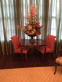 Mahogany game table pictured with exceptional large floral arrangement and pair of traditional chairs
