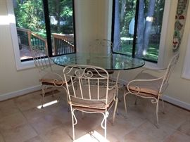 Wrought iron oval shaped glass top table and four chairs. Chairs have wood seats.