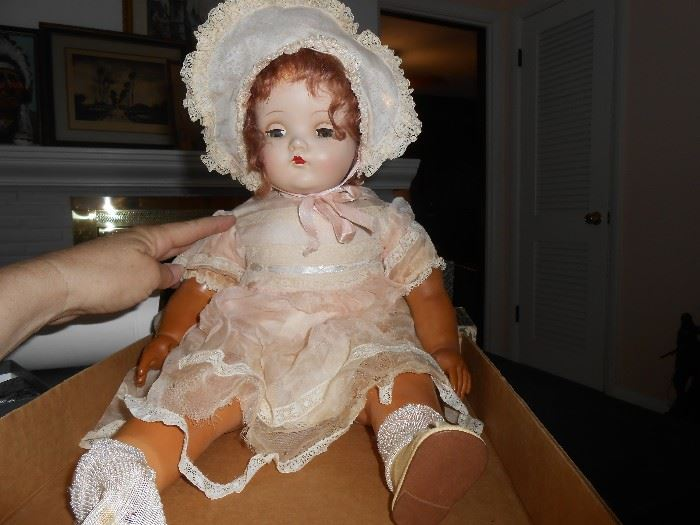 Madame Alexander Little Genius doll shows natural wear.         Her eyes open and close. The doll has composition head,        hands, feet and a cloth body. Clothing bears the original    Madame Alexander tag. She is 22 inches long. 1933.                      This doll has a crier that is no longer working.