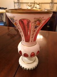 One of two antique matching Bohemian cut to Opaline with enameling footed vases