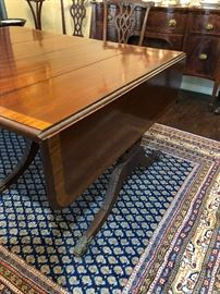 This antique circa 1900 English Regency dining table has a drop leaf feature at both ends.  It has three leaves which in place  extend it to 10 ft 10 1/2 ins in length.   It is 3 ft and 11 1/2 ins wide and 2 ft 5 ins tall with period correct brass caster wheels