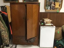 Armoire and small refrigerator, sleeping bags and men's Gun cases and hunting clothing. Pictures and mirrors along the walls.