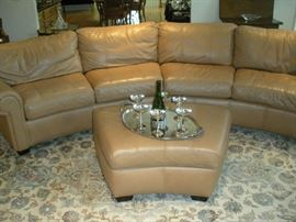 Living Room:  The two-piece leather BERNHARDT sectional with attached back cushions and ottoman are in very, very good condition!  Each curved section is 7 feet long, for a total curved piece of 14 feet. The silver tray and six silver champagne stems are priced separately.  (Six more silver champagne stems are nearby.)  The area rug is very large as noted in the next photo.