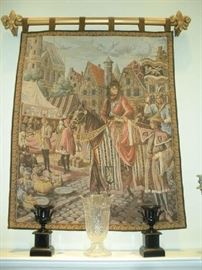 "Living Room:  A vintage machine made wall tapestry of a 15th century French genre scene depicting a Medieval outdoor market, tents, and vendors selling their goods  (39-1/2"" X 50"" not including rod pockets) hangs on a  Fleur de Lis rod.  On the mantel are a large crystal vase and a pair of cast iron garniture vases that were originally part of a clock."