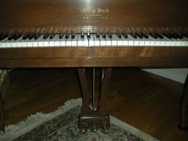 Living Room: You can now see the GEORGE STECK brand as well as the keyboard and foot pedals of the baby grand piano.