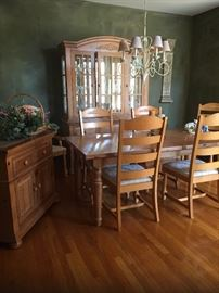 Honey stained wood dining table with two leaves and table top pads for protection. Glass china cabinet, serving buffet, and six chairs.