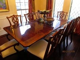 Beautiful dining table with 8 chairs.  High sheen on table.  Has custom table pads.