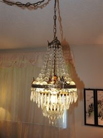 Hollywood Regency Chandelier hanging over the round bed