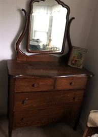 Beautiful Antique Bureau with Slanted/Tilted Mirror and  4 drawers. Very Nice Find.  Sitting on the Dresser is a 1910 edition of Alice's Adventures In Wonderland.