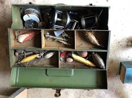 Antique fishing lures with reels, all in an old tin fishing tackle box.  A must see and have for the fishing collector.
