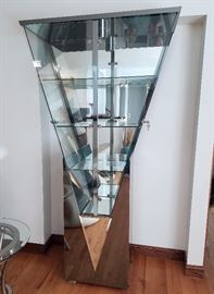 """Ultra-modern, geometric, inverted pyramid curio cabinet.  Constructed of stainless steel, glass and mirrors.  Lighted, 2-doors with keys, 78"""" tall, 16"""" deep, 20"""" wide at bottom, 42"""" wide at top."""