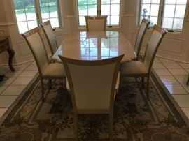 Formal dining room table with 8 uphostered chairs. This table has a marble look top.