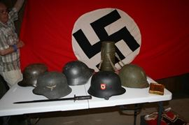 WWII German helmets and dagger with Nazi banner/flag in background.