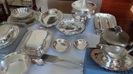 Many silver plate serving dishes and ice bucket