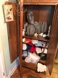 a cabinet full of the unusual- linens, glass and table top items. Check out our friend who looks like he is from Easter Island! Not to mention the coat rack