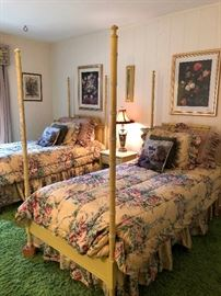 Precious yellow 4-poster twin beds have a matching nightstand; rose fabric bedding