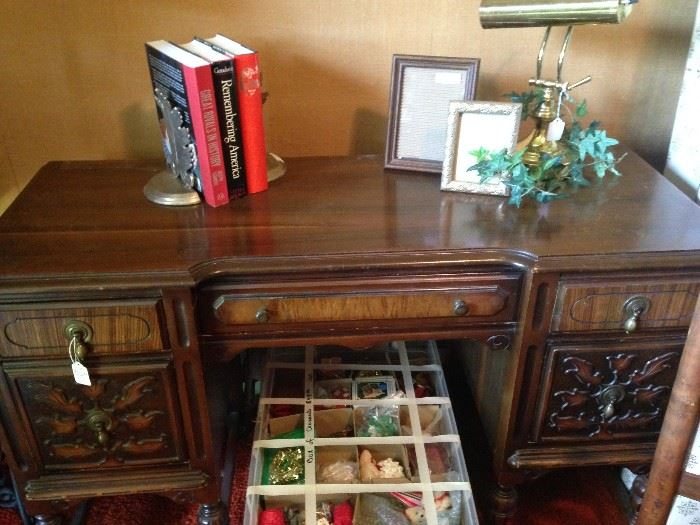 Antique desk; books; frames; desk lamp; below -  Christmas ornaments