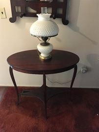 a beautiful lamp table with milk glass hurricane-style lamp