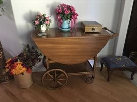 Antique tea cart with small drawer and glass tray.  Cross stitched foot stool, silk flowers.