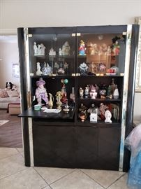 Black lacquer curio cabinet with clown figures.