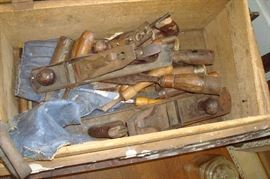 Old wood chest containing planes and wood chisels.