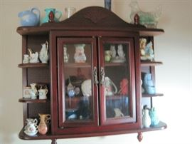 small pitchers in display cabinet