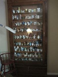 collection of small pitchers in tall narrow cabinet & youth chair