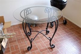 Wrought iron patio table with glass top.