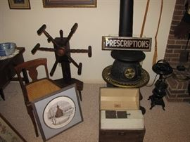 One of two Spinning wheels, cast iron stove, antique glass Prescription sign.