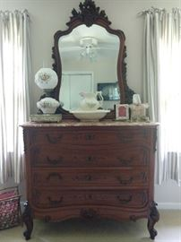Antique French hand carved walnut dresser, with matching mirror and marble top.