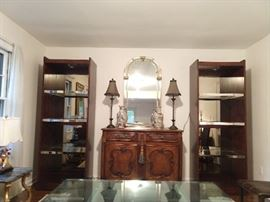 """Pair of large mahogany lighted 3-glass shelf/chrome strip curio cabinets, with smoked glass backing, are from Hickory White's (Hickory, NC) """"Gramercy"""" collection."""