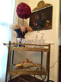 Love, Love, Love this vintage Parisian brass dessert cart! What makes this one so unique is the glass section below that is completely enclosed, + the glass rod handle is HOT! How that koi jumped in there, I have no idea. Celosia topiary lording over Waterford crystal decanters,  while being stared down by the oil on canvas seafood still life, 1888, by listed French artist, Ernest Honnorat.