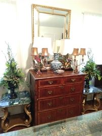 Antique English banded wood 5-drawer chest, with large gold wood/beveled glass mirror, flanked by a pair of vintage Italian Florentine side tables with green marble tops.