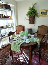 "Small, round breakfast table, with three side chairs,  old French market basket fern wall hanging.                               The ""breakfast table"" is a ca. 1810 French bread table, from Jane Marsden Antiques, purchased in the mid-90's when everyone had money, for $2,450.00.                                                                                         I'm in the wrong end of this business!"