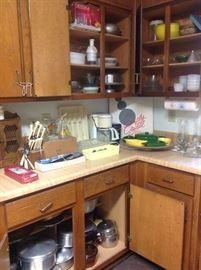 Multiple sets of vintage flatware, pots and pans and kitchen gadgets.